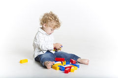 Cute toddler is building with legos