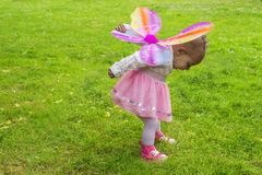Cute toddler with butterfly wings. Adorable toddler wearing butterfly wings playing in the grass Stock Images