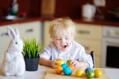 Cute toddler child hunting for easter egg on Easter day. Little boy celebrate Easter at home Stock Photo