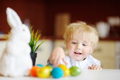 Cute toddler child hunting for easter egg on Easter day Royalty Free Stock Photos