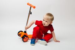 Cute Toddler child in a red t-shirt fell from a scooter and sits, shooting in the studio on a white background royalty free stock photography