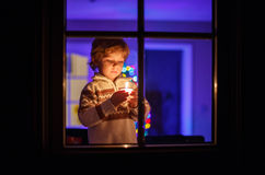 Cute toddler child standing by window at Christmas time and hold Royalty Free Stock Images