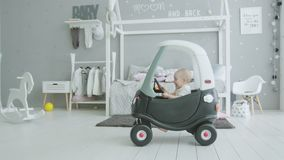 Joyful infant girl sitting in baby car at home. Cute toddler child trying to drive baby car, turning steering wheel, pushing horn enjoying play in nursery at stock video footage