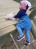 Cute toddler in city playground. Cute toddler with pink summer hat playing at city playground and climbing on yard toy Stock Image