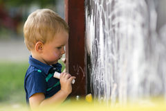 Cute toddler drawing with chalk outdoors. Creative cute toddler drawing with chalk outdoors on a drawing board Royalty Free Stock Photo