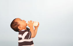Cute toddler drinking milk. Cute Asian baby boy drinking milk from a bottle Stock Photos