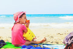 Cute toddler eating fresh summer peach  on the beach Royalty Free Stock Photo