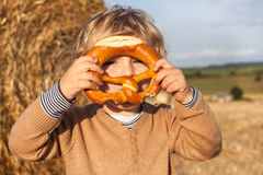 Cute toddler eating German pretzel on goden hay field Stock Image