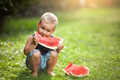 Cute toddler eating a slice of watermelon. Cute toddler sitting outdoords and eating a slice of watermelon royalty free stock photo