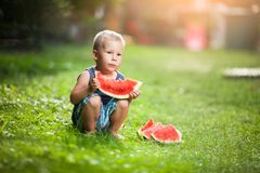 Cute toddler eating a slice of watermelon royalty free stock images
