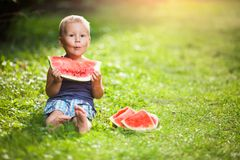 Cute toddler eating a slice of watermelon stock photos