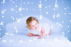 Cute toddler girl in a bedroom. Adorable toddler girl with curly hair wearing a beautiful white dress playing in a bedroom with Christmas lights Stock Images