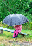 Cute toddler girl with big umbrella sitting in the garden by rai Stock Photo