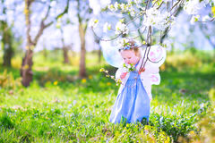 Cute toddler girl in a blooming apple garden Stock Photos