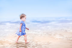 Cute toddler girl in blue dress walking on beach stock photography