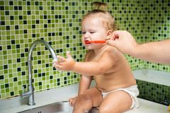 Cute toddler girl brushing her teeth in the bathroom. Cute baby sitting in the sink. Dad helps to brush the child teeth royalty free stock image