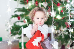 Cute toddler girl checking her Christmas stocking Stock Photos