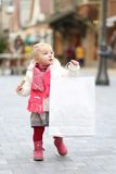 Cute toddler girl at Christmas shopping street Royalty Free Stock Photos