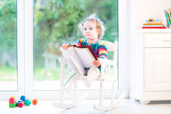 Cute toddler girl in a colorful knitted dress playing with a boo Stock Photography