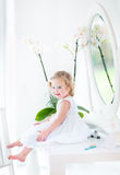 Cute toddler girl with curly hair playing with make up Stock Photos