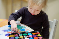 Cute toddler girl drawing with paints in preschool Stock Photo