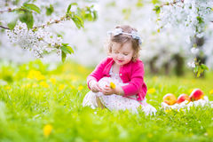 Cute toddler girl eating apple in a blooming garden Stock Image