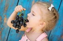 Cute toddler girl eating grapes royalty free stock photo