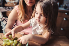 Cute toddler girl eating grapes with mother on the kitchen Royalty Free Stock Photos