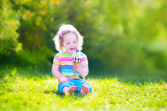 Cute toddler girl eating ice cream in a garden Royalty Free Stock Photo