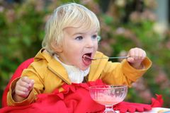 Cute toddler girl eating ice cream outdoors in cafe Royalty Free Stock Image