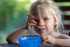 Cute toddler girl eating ice cream with a spoon from a bowl. royalty free stock photo