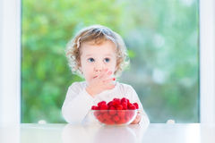 Cute toddler girl eating raspberry at white table Royalty Free Stock Image