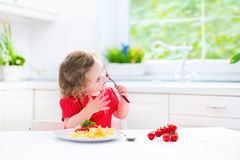 Cute toddler girl eating spaghetti in a white kitchen Stock Photography