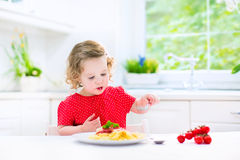 Cute toddler girl eating spaghetti in a white kitchen Stock Photos