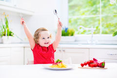 Cute toddler girl eating spaghetti in a white kitchen