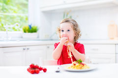 Cute toddler girl eating spaghetti in a white kitchen Royalty Free Stock Photography