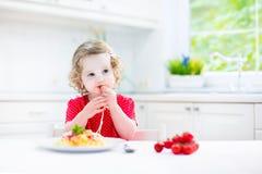 Cute toddler girl eating spaghetti in a white kitchen Stock Photo