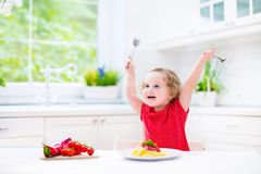 Cute toddler girl eating spaghetti in a white kitchen Royalty Free Stock Image
