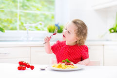 Cute toddler girl eating spaghetti in a white kitchen royalty free stock photos