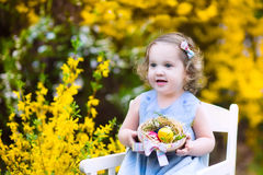 Cute toddler girl enjoying easter egg hunt in garden Stock Images