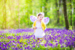 Cute toddler girl in fairy costume in bluebell forest. Adorable toddler girl with curly hair wearing a fairy costume with purple wings and yellow dress is Stock Photos