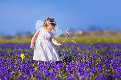 Cute toddler girl in fairy costume in a flower field. Portrait of an adorable toddler girl in a magic fairy costume and flower crown in her curly hair playing Royalty Free Stock Photos