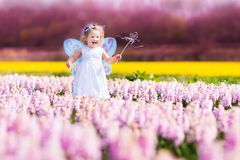 Cute toddler girl in fairy costume in a flower fie. Portrait of an adorable toddler girl in a magic fairy costume and flower crown in her curly hair playing with stock photography