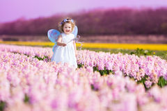 Cute toddler girl in fairy costume in a flower field. Portrait of an adorable toddler girl in a magic fairy costume and flower crown in her curly hair playing Stock Images