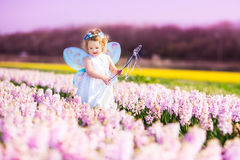 Cute toddler girl in fairy costume in a flower field. Portrait of an adorable toddler girl in a magic fairy costume and flower crown in her curly hair playing Royalty Free Stock Photo