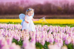 Cute toddler girl in fairy costume in a flower field. Portrait of an adorable toddler girl in a magic fairy costume and flower crown in her curly hair playing Royalty Free Stock Images