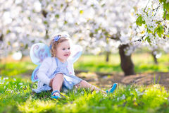 Cute toddler girl in fairy costume in fruit garden. Adorable toddler girl with curly hair and flower crown wearing a magic fairy costume with a blue dress and Royalty Free Stock Photography