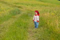Cute toddler girl with funny face in a meadow Stock Photo