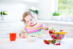 Cute toddler girl having breakfast drinking juice Royalty Free Stock Image
