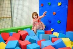 Cute toddler girl having fun in indoor leisure center for kids Stock Photos